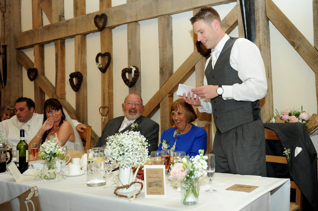 The Best Man starts his speech with a a few one liners to warm up the audience in this relaxed wedding photo taken at the wonderful Gate Street Barn near Guildford Surrey
