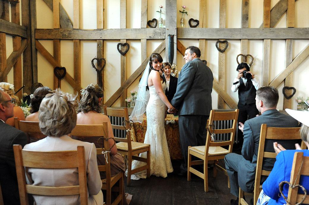 The Bride turns around with excitement and a big smile as she is married in this happy wedding picture taken by Surrey Lane wedding photography at Gate Street Barn in Bramley