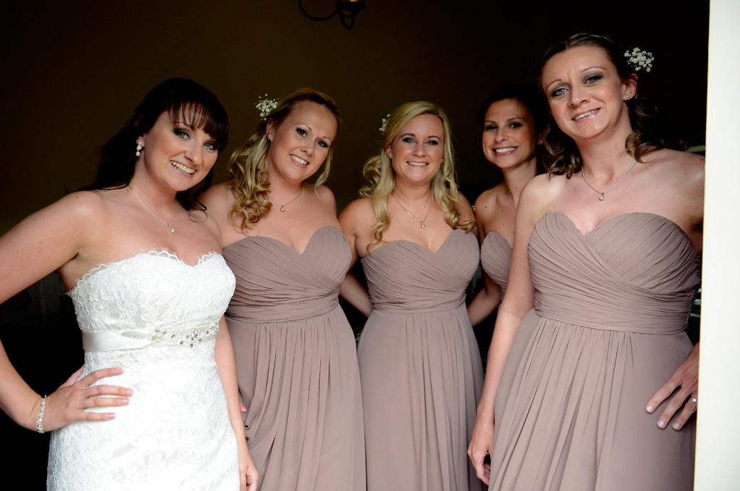 The lovely relaxed and happy wedding photograph of the smiling Bride with her Bridesmaids all ready in their beautiful dresses at Gate Street Barn a delightful Surrey wedding venue