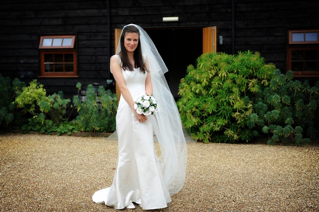 Lovely Bride poses with her wedding bouquet on the gravel outside the delightful Surrey wedding and reception venue Gate Street Barn in the village of Bramley Guildford