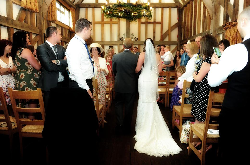 The Bride walking down the aisle on the arm of her father in this taken from the back wedding photograph at Gate Street Barn an enchanting Surrey wedding venue