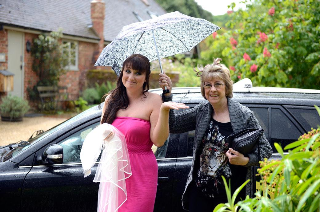Lovely human moment captured in this  wedding photograph as the Bride and mother get out of the car to be met with a sudden downpour at Surrey wedding venue Gate Street Barn