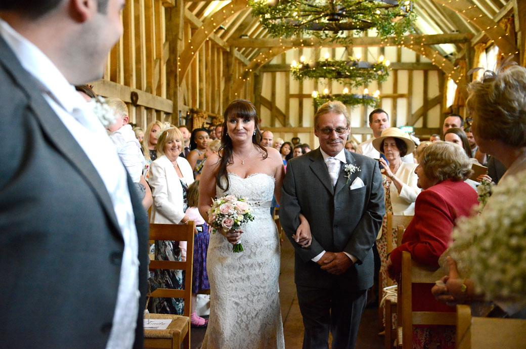 The Bride and her Father both smiling as they approach the Groom in the wedding picture taken at the enchanting Gate Street Barn by a Surrey Lane wedding photographer