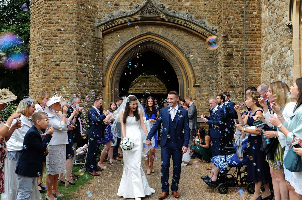 Fun wedding photograph of a couple walking down a line of guests blowing hundreds of bubbles at them on route to  their Gate Street Barn wedding reception in Bramley Surrey