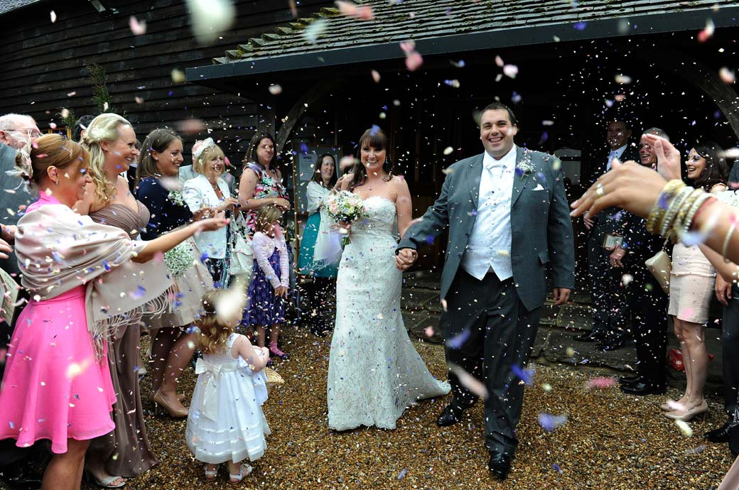 The happy newly-weds walk under a shower of confetti in this happy colourful wedding picture captured by a Surrey Lane wedding photographer at the pretty Gate Street Barn