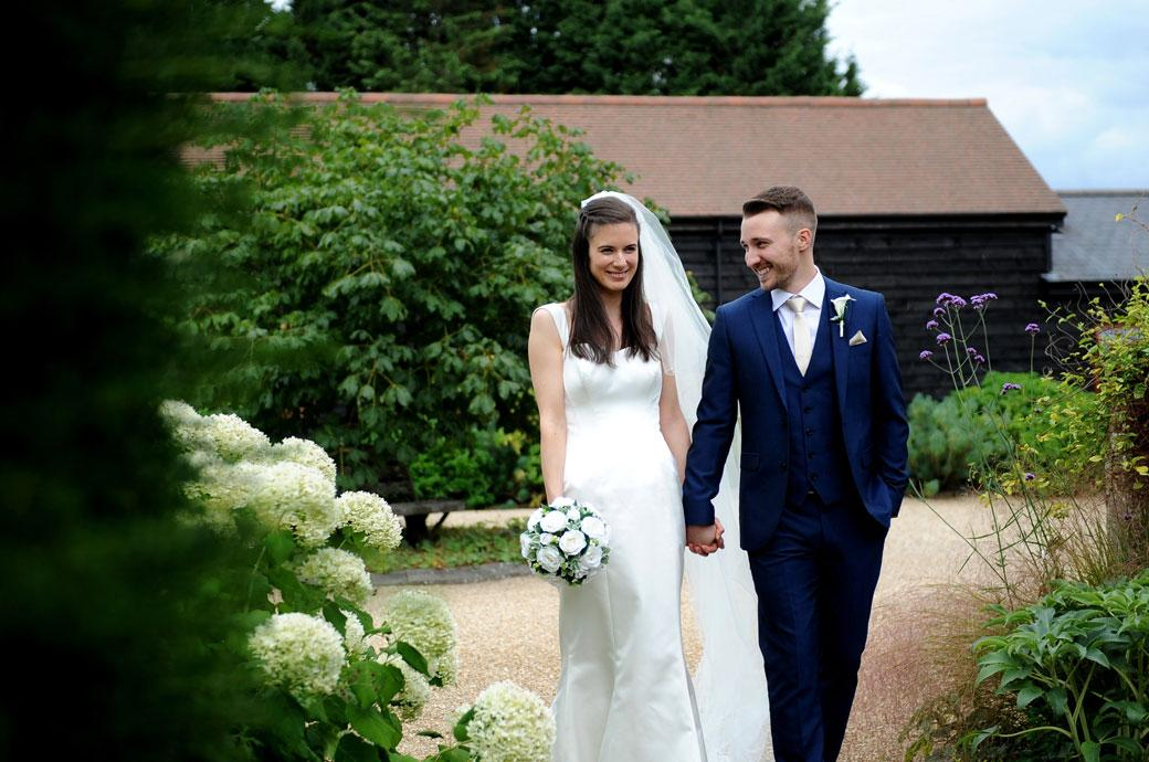 Happy in love wedding couple pictured here as they walk through the pretty yard at the lovely Gate Street Barn a Surrey wedding venue built after the great storm of 1987