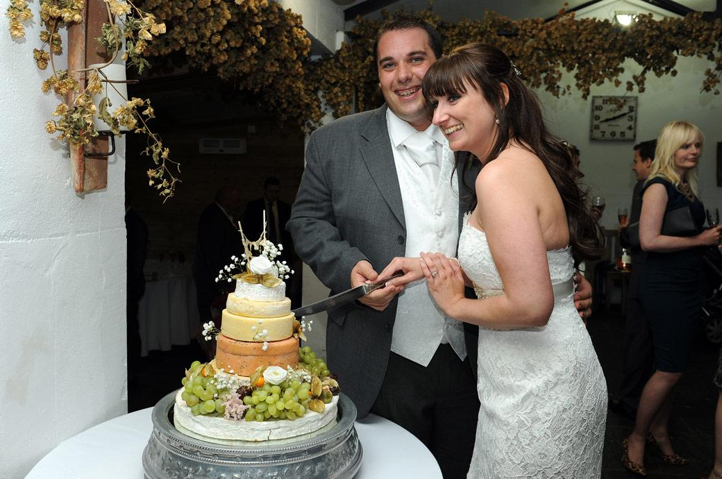 Poised ready to cut into their cheese wedding cake in this fun wedding photo taken at the wonderful Surrey venue Gate Street Barn in the  Pheasantry