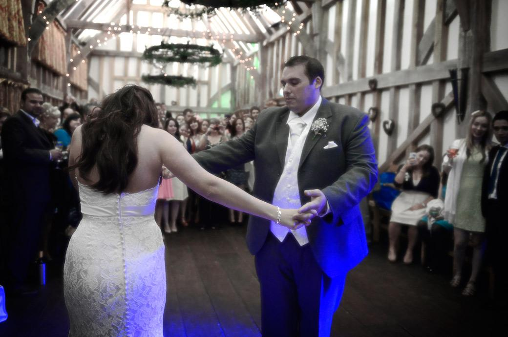 The Groom gently swirls his new wife around the dancefloor in front of an admiring audience during the first dance in this wedding picture from Gate Street Barn Surrey