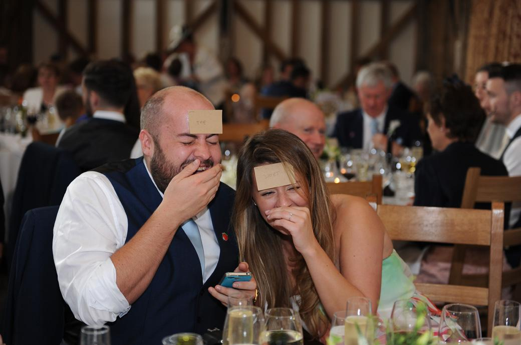 Gate Street Barn wedding guests in hysterics as they play a table party game with names stuck on their foreheads captured by a Surrey lane wedding photographer