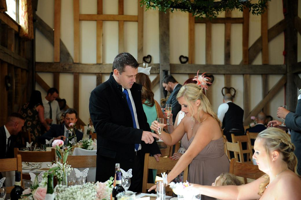 Guests come in to find their seats for the wedding breakfast in this informal wedding photo captured by Surrey Lane wedding photographers at the beautiful Gate Street Barn