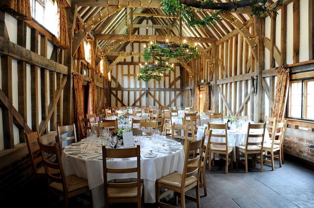 The beautiful barn interior pictured here dressed and ready for the wedding breakfast at the interestingly recently built Surrey wedding venue Gate Street Barn in Bramley village