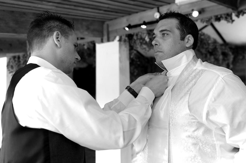 The Groom gets help with his tie from his Best man in this wedding photo taken as they get ready in The Pheasantry at Gate Street Barn by Surrey Lane wedding photographers