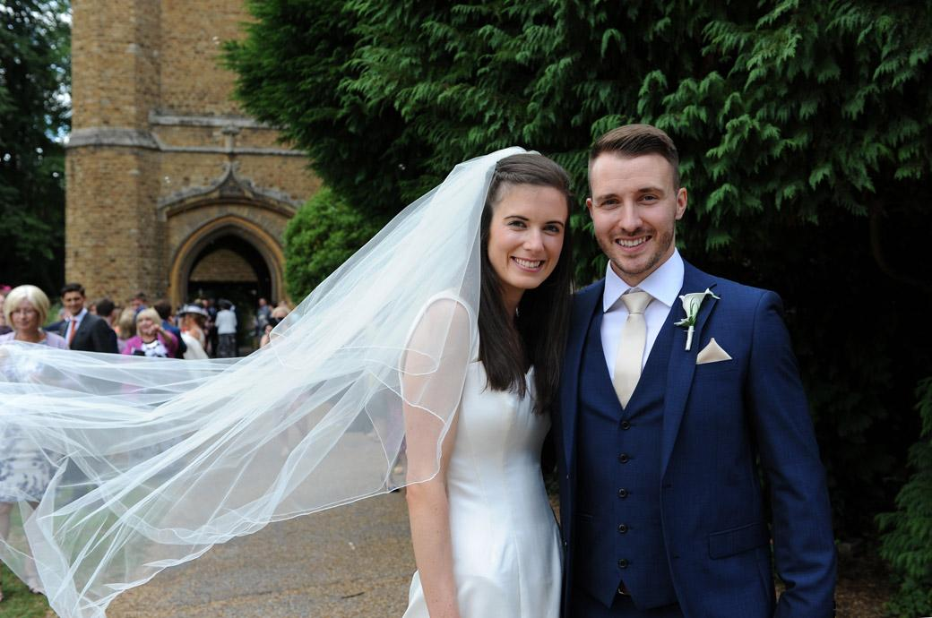 Happy smiling newlyweds in this sweet wedding picture taken after their church wedding ready to leave for the lovely Surrey wedding venue in Guildford Gate Street Barn