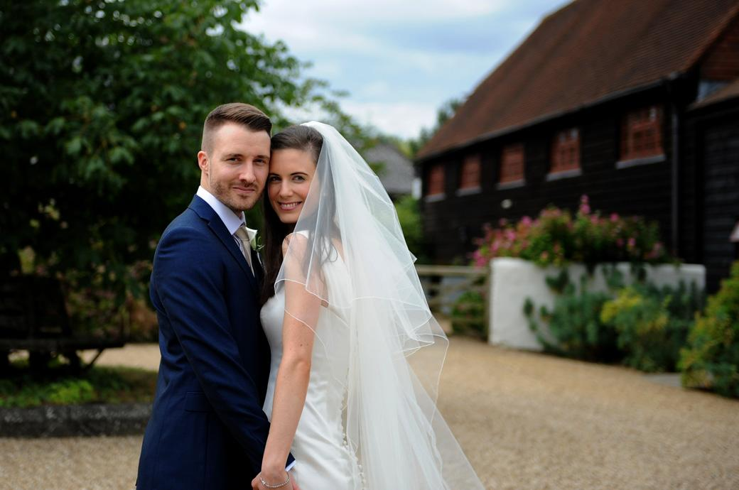A happy bride rests her head on her proud Groom captured by a Surrey Lane wedding photographer in the picturesque yard  at the beautiful Gate Street Barn in Bramley Guildford