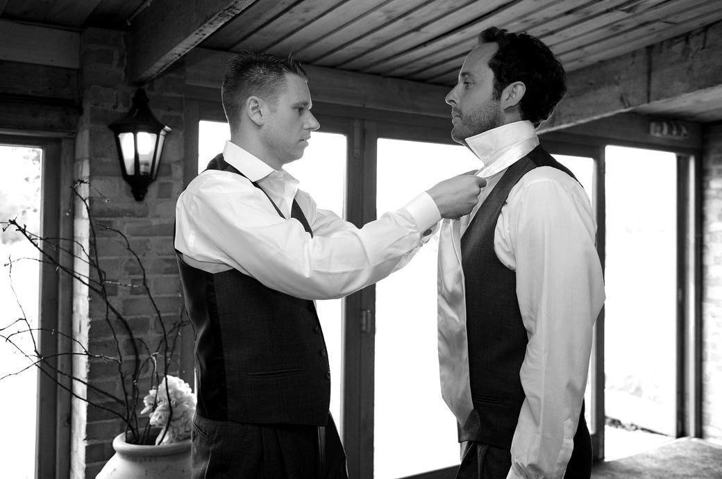 Best man helps an usher on with his tie in this informal natural wedding picture taken at the delightful Surrey wedding venue Gate Street Barn in The Pheasantry