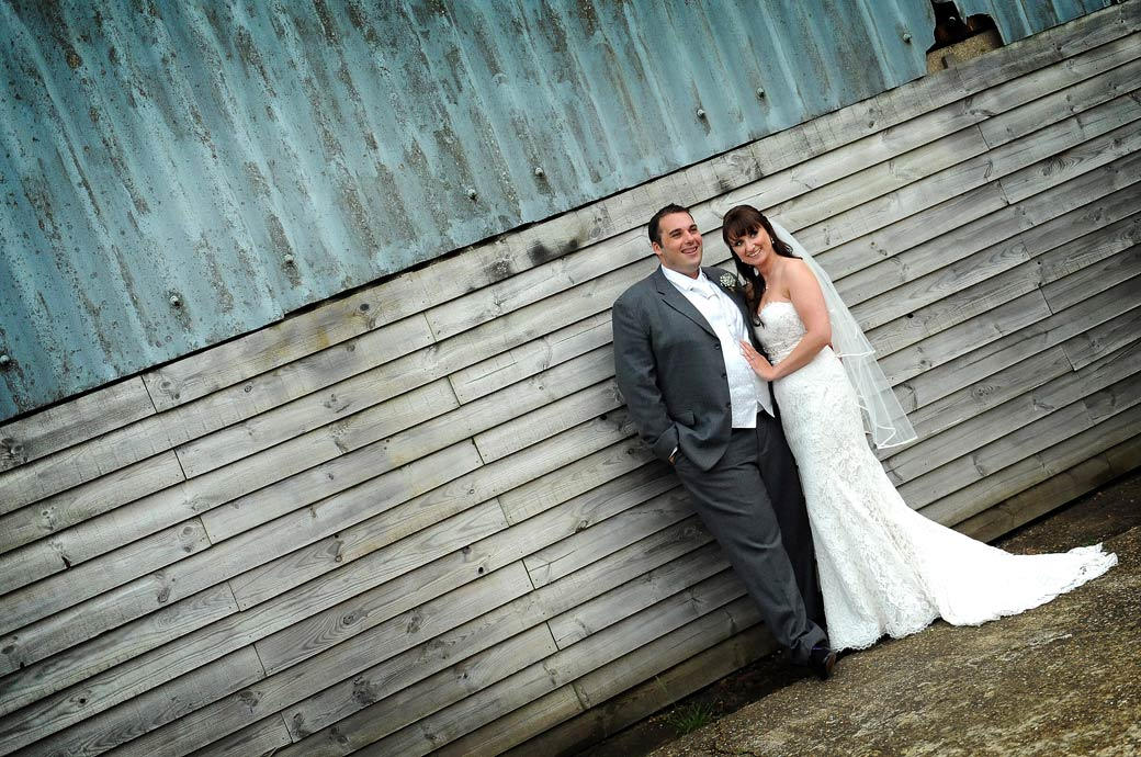 Newly-weds strike a relaxed happy pose in front of the distressed wooden and corrugated iron building wall in this wedding photo from Gate Street Barn in Surrey