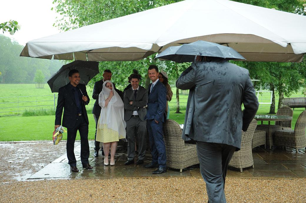 Laughing guests watch someone covering their head walking for cover from the heavy rain in this funny wedding photo taken at Gate Street Barn near Guildford Surrey