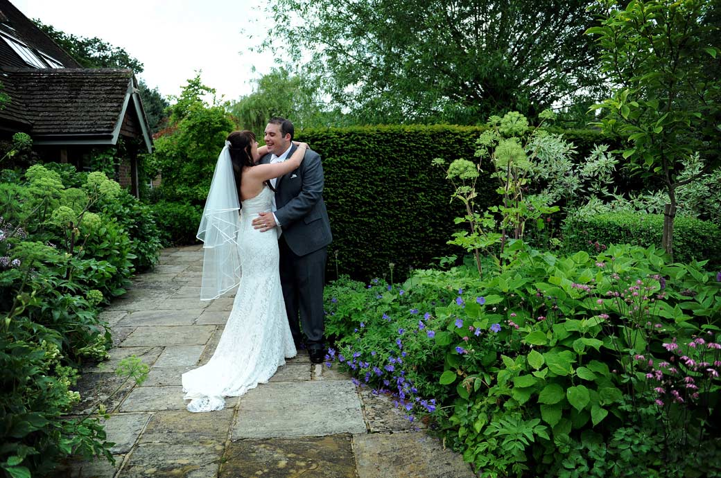Happy loving embrace between the newly-weds in this wedding photo taken in the pretty farm garden at the lovely Gate Street Barn a memorable Surrey wedding venue
