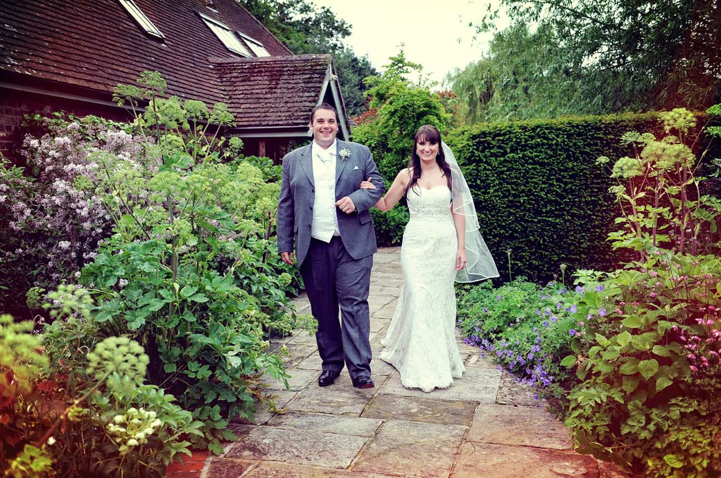 Wedding photograph of a beaming couple walking arm in arm along the flagstones of the pretty little farm garden taken at Surrey wedding venue Gate Street Barn