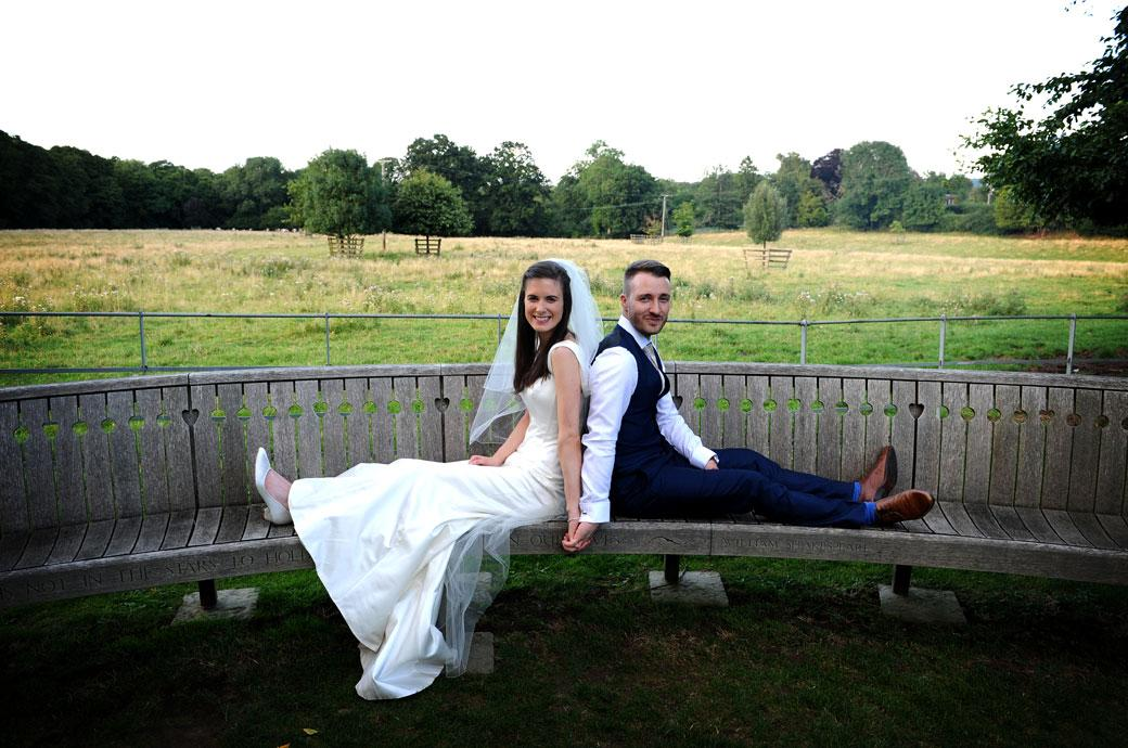 Wedding couple sitting back to back on the large wooden bench and holding hands in this romantic wedding photo taken at Gate Street Barn in Bramley Surrey
