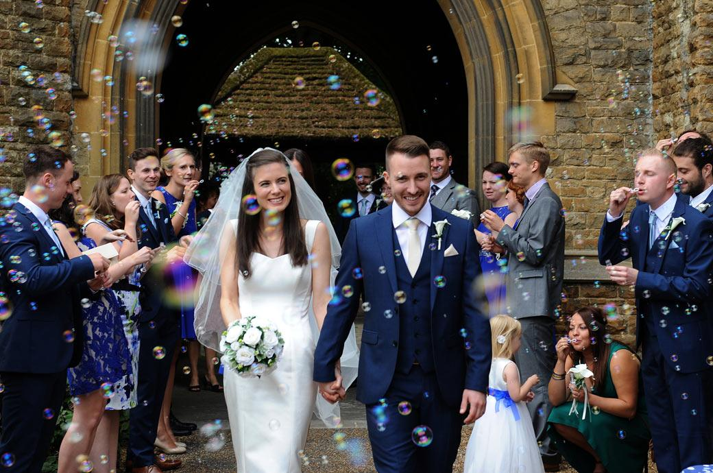 All fun and smiles for the newlywed couple as they enjoy some bubbles outside the Church before leaving for the relaxing Surrey wedding venue  Gate Street Barn in Bramley village