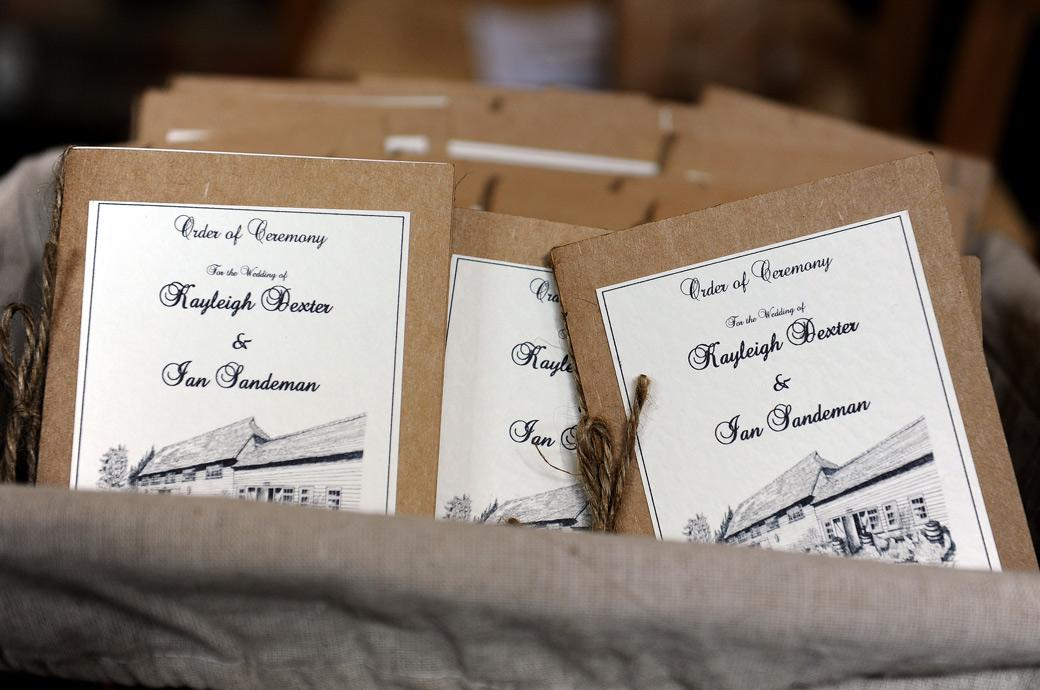 A box containing the rustic looking orders of service in this wedding photograph ready to hand out to the guests as they arrive at the delightful Surrey wedding venue Gate Street Barn