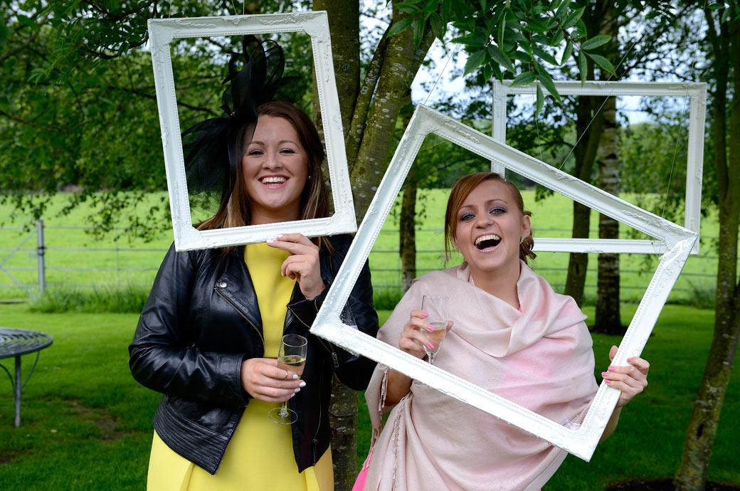 Guests posing through picture frames hanging from a tree in this fun wedding photograph taken at the idyllic Gate Street Barn located near Guildford in the Surrey Hills