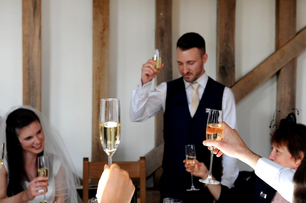 Raised glasses during the champagne toast by the groom during the wedding speeches at the lovely Surrey wedding venue in Bramley Guildford Gate Street Barn