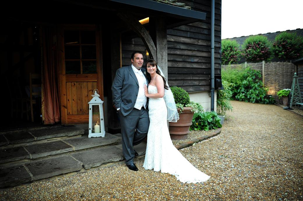 Another relaxed wedding photograph of the newly-wed couple as they stand smiling at the front entrance of the idyllic Surrey wedding venue Gate Street Barn