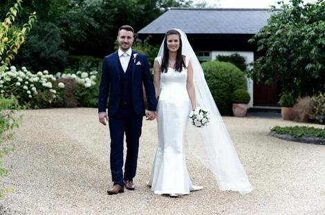 Happy handsome newlywed couple smiling as they walk along the gravel hand in hand at the lovely Surrey wedding venue Gate Street Barn in the village of Bramley Guildford