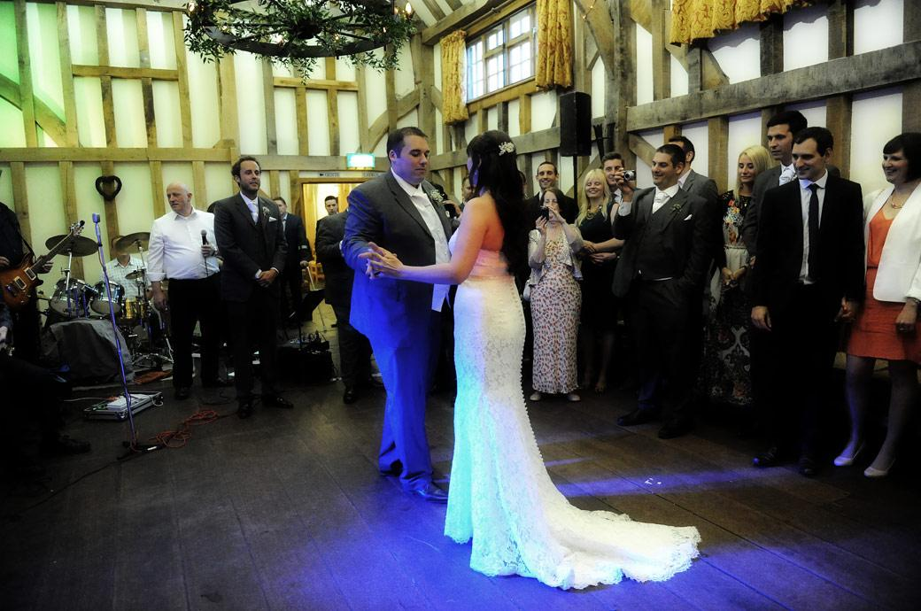 The wedding couple start the first dance in this wedding photograph captured by Surrey Lane wedding photography at Gate Street Barn in Bramley near Guildford