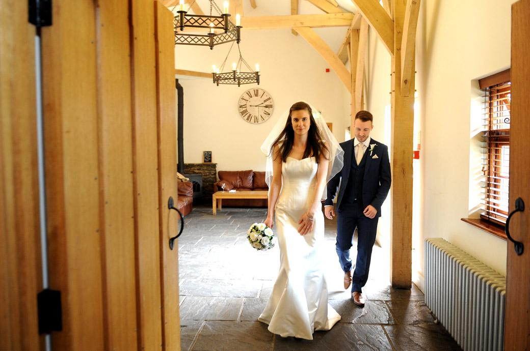 The Bride and Groom go into the main guest area to inspect the wedding breakfast settings captured by a Surrey lane wedding photographer at Gate Street Barn
