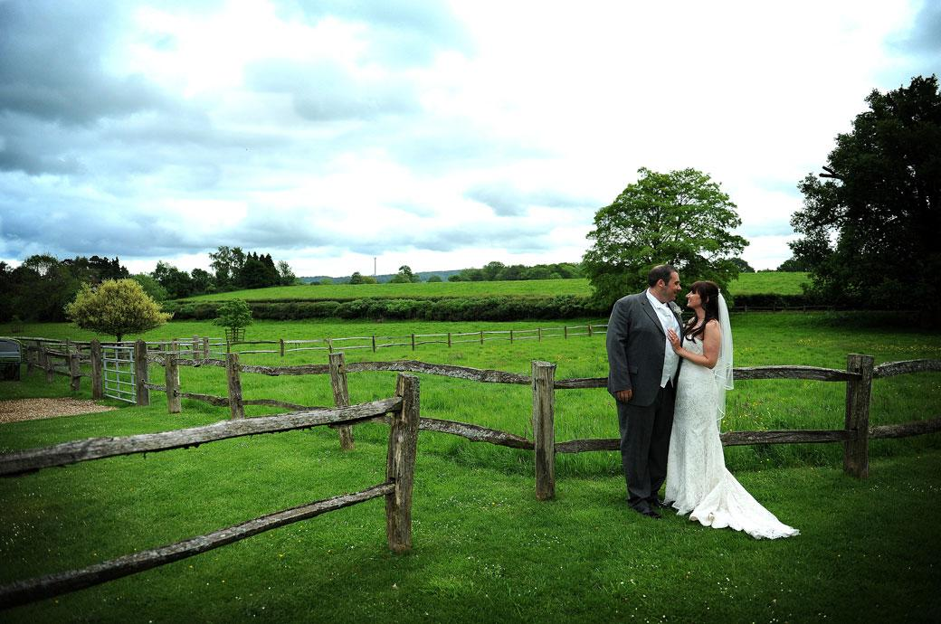 Couple share an intimate moment as they stand in front of a beautiful background of luscious green fields and old wooden fences at Surrey wedding venue Gate Street Barn
