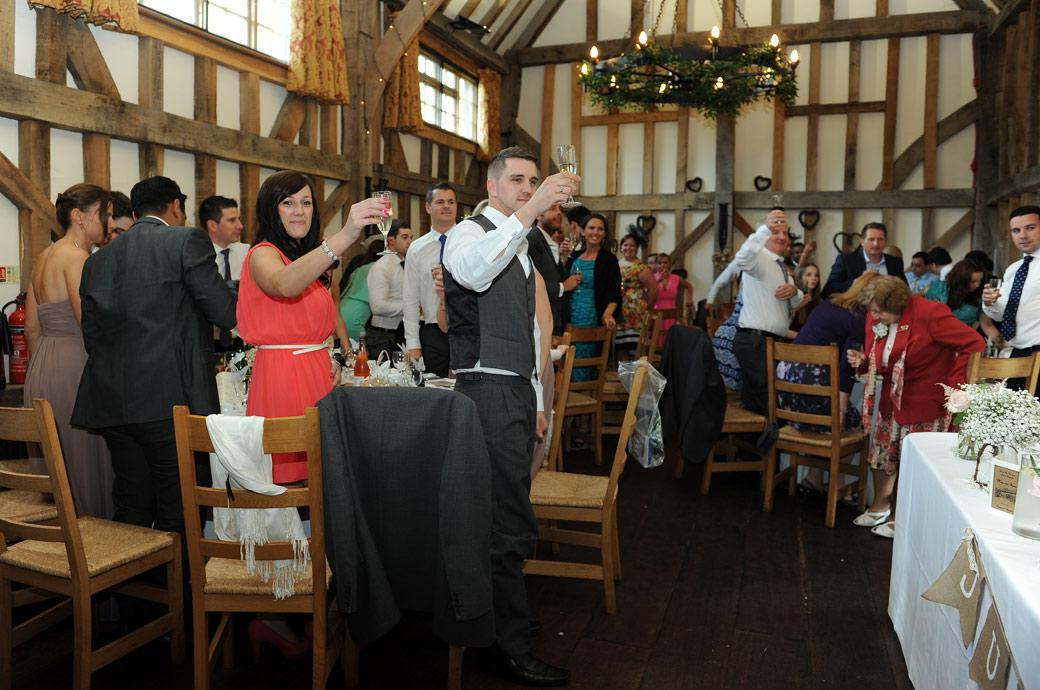 All the guests raise their glasses to toast the happy newly-weds in this wedding photograph taken at the magical Gate Street Barn in Bramley Surrey