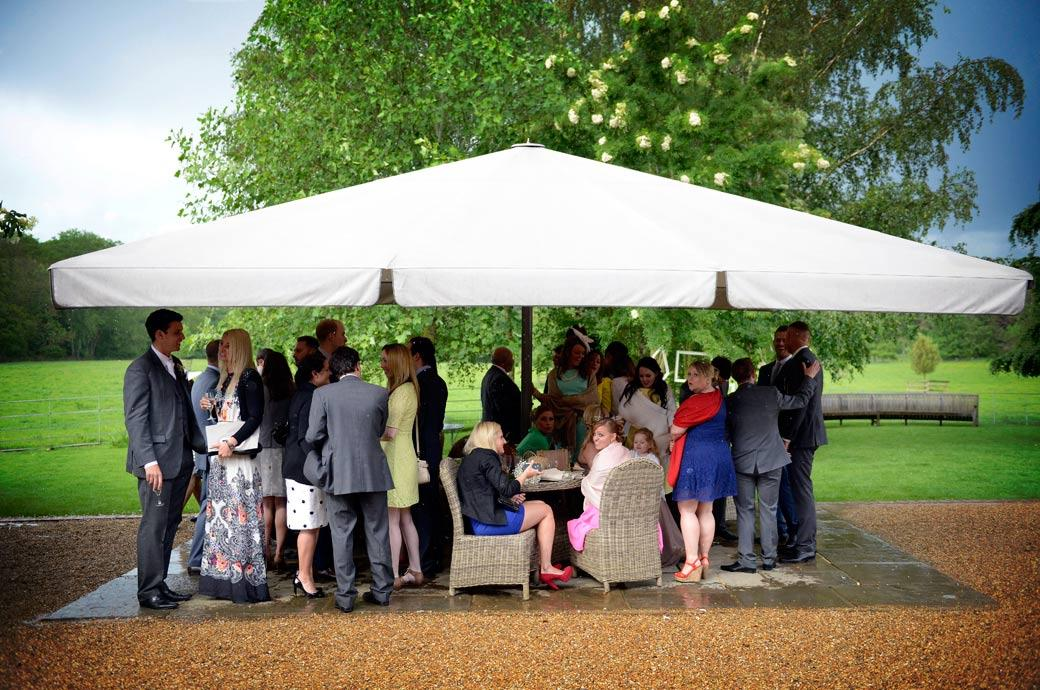 Guests all chatting under the large garden canopy Gate Street Barn out of the rain in this bright wedding picture captured by Surrey Lane wedding photography