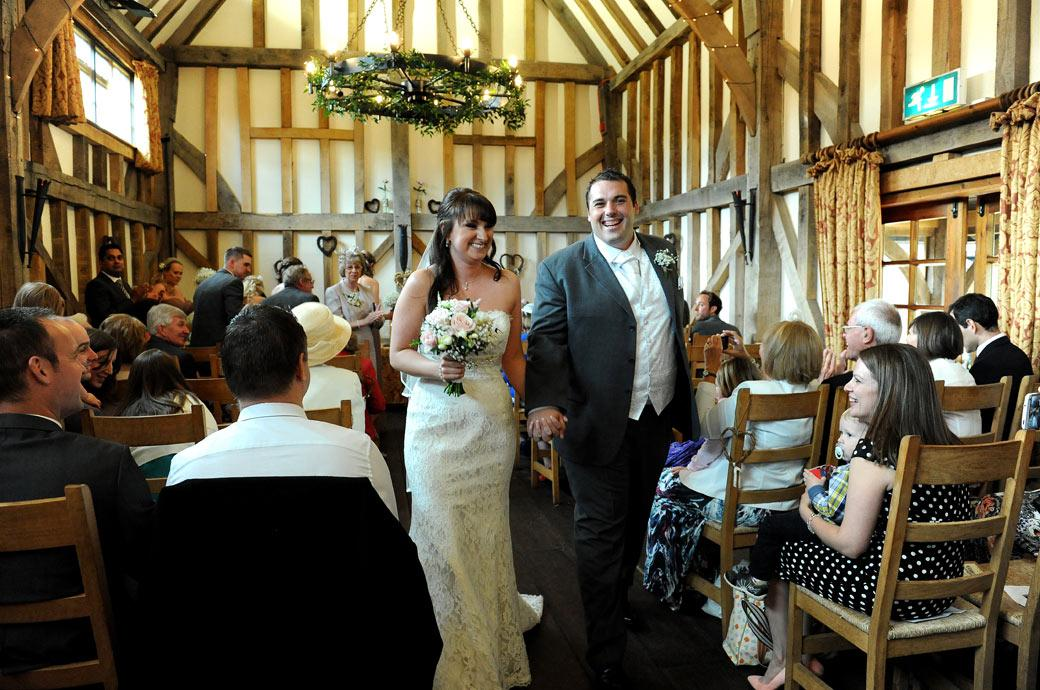 All laughter for the Bride and Groom as they walk down the aisle as husband and wife in this warm wedding photograph captured at hidden Surrey wedding venue Gate Street Barn