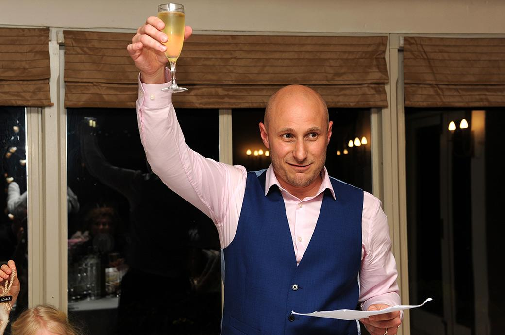 Groom at Surrey venue Gatton Manor in Dorking raises his glass of champagne and toasts his wife at the end of his wedding speech in the Lakeside Room