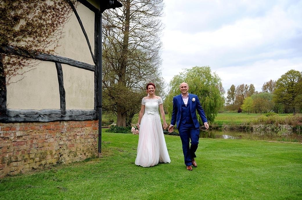 Handsome smiling Bride and groom walking across the lawn during their romantic walk of the grounds at Gatton Manor a popular Surrey wedding venue