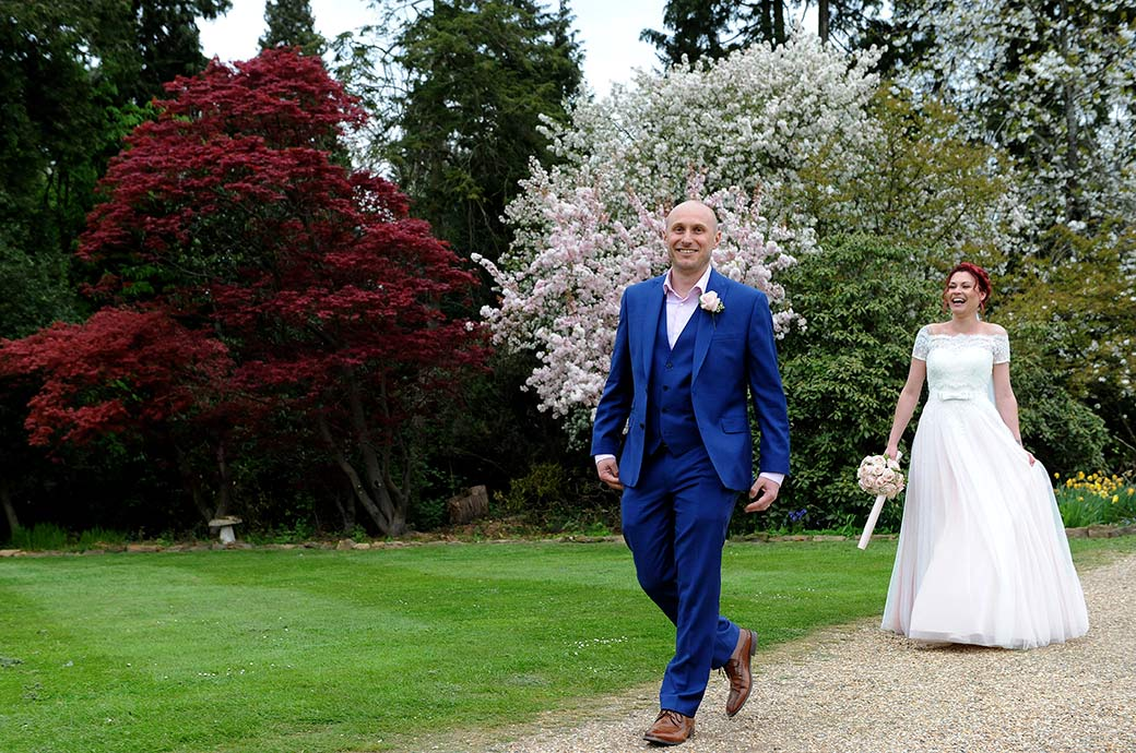 All smile sand laughter at Surrey wedding venue Gatton Manor as the Bride and groom have fun walking along a path from the Victorian Gardens