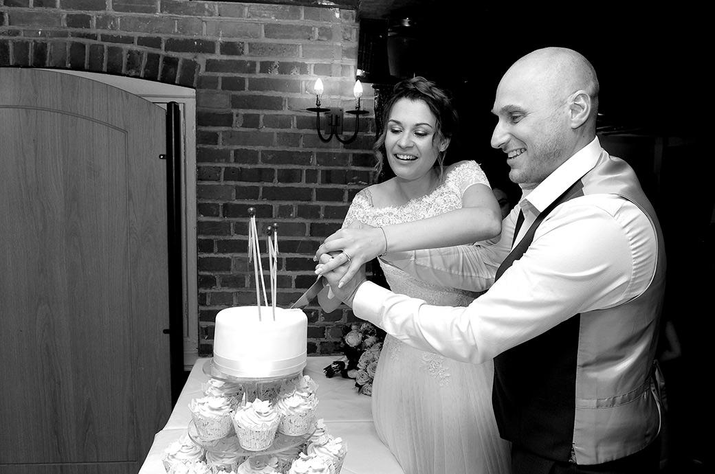 Smiling Bride and groom captured as they are about to cut their wedding cake at the Surrey wedding venue Gatton Manor in the Lakeview Room