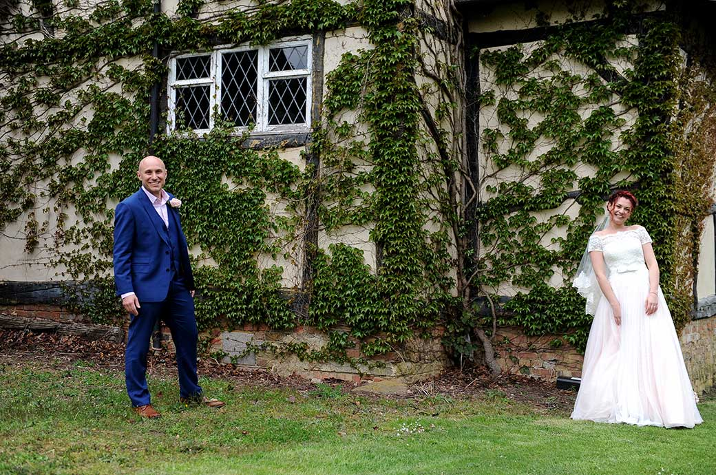 Happy smiling Bride and groom captured in the wedding photo standing by the ivy covered wall of Surrey wedding venue Gatton Manor