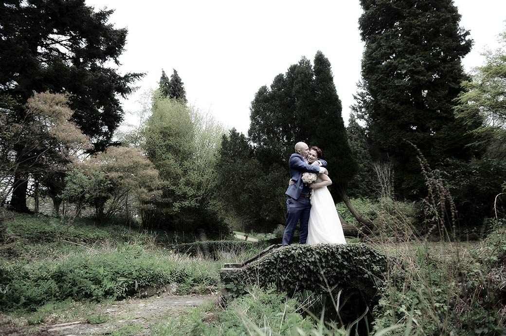 Groom hugs and kisses his smiling Bride at the Surrey wedding venue Gatton Manor in Dorking as they stand on a small ivy covered bridge crossing a stream