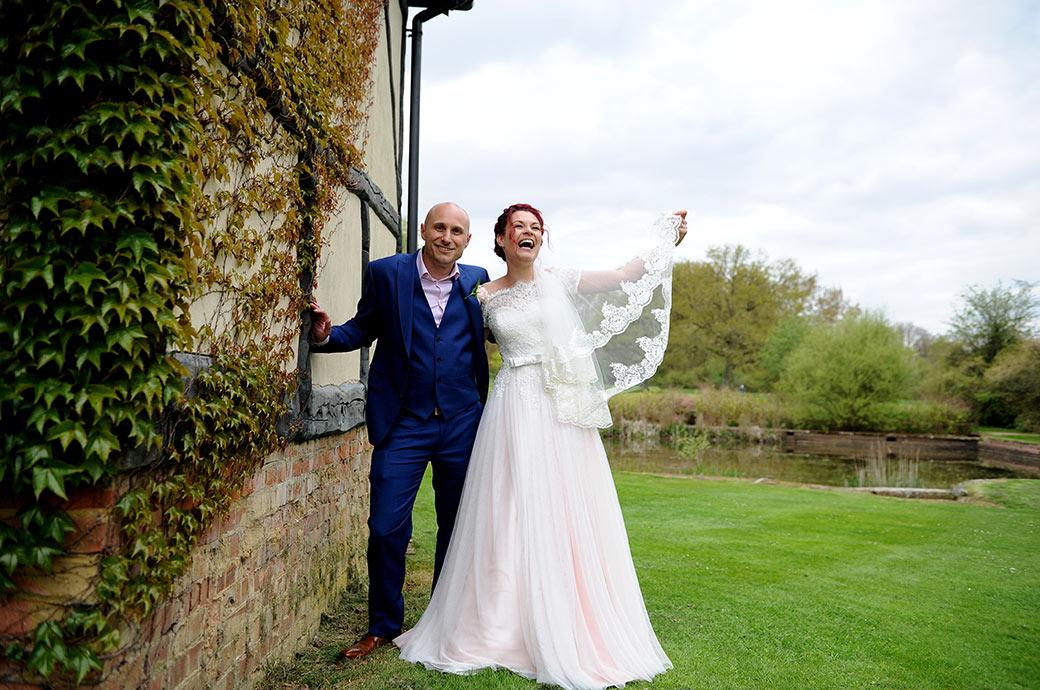 Content Groom smiles as his lovely Bride laughs on the lawn during their walk around Surrey wedding venue Gatton Manor in Dorking