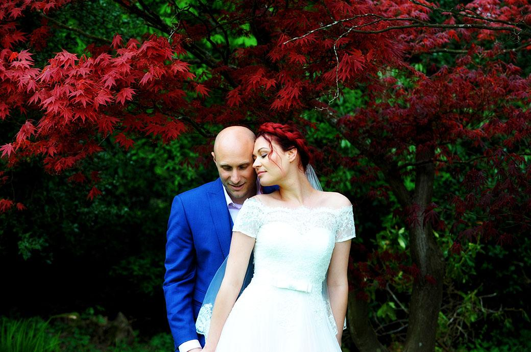 Lovely romantic scene captured at Surrey wedding venue Gatton Manor in Dorking of Bride with red hair sharing a moment with the groom by a similarly coloured red tree