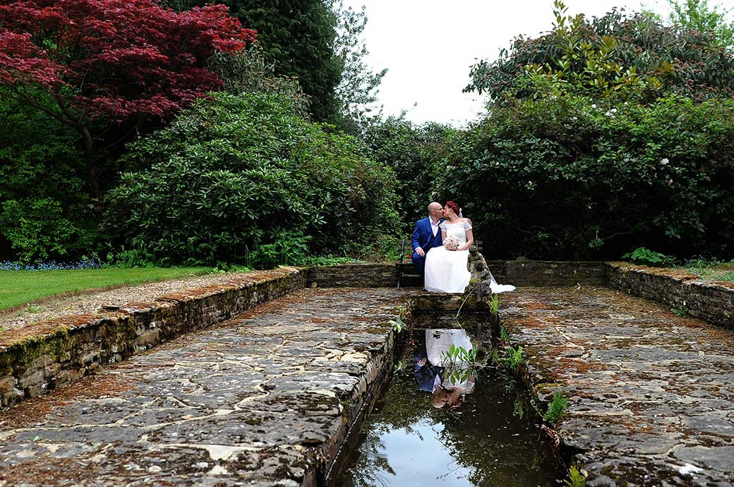 Bride and groom romantically kiss outside at Surrey wedding venue Gatton Manor on a stone bench at the end of the flagstones of the Victorian fountain