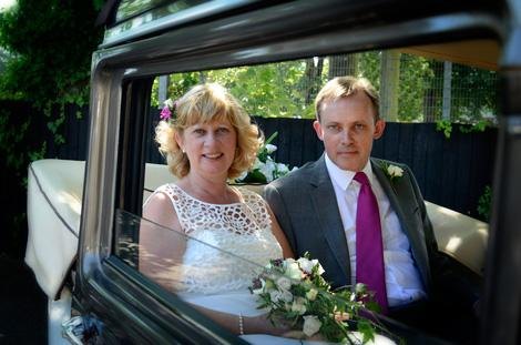 Relaxed and happy Bride and Groom wedding picture taken as they sit in their wedding car at the Surrey wedding venue Glenmore House in Surbiton