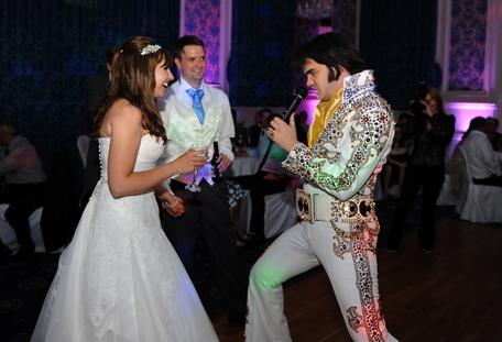 An excited Bride and groom in this wedding picture dancing with Elvis on the in the grand Elizabethan Suite at Surrey wedding venue  Glenmore House in Surbiton