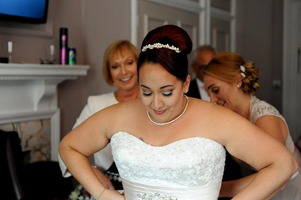A happy and excited Bride being assisted with putting on her wedding dress captured at the lovely relaxed Gorse Hill Woking by a Surrey Lane wedding photographer
