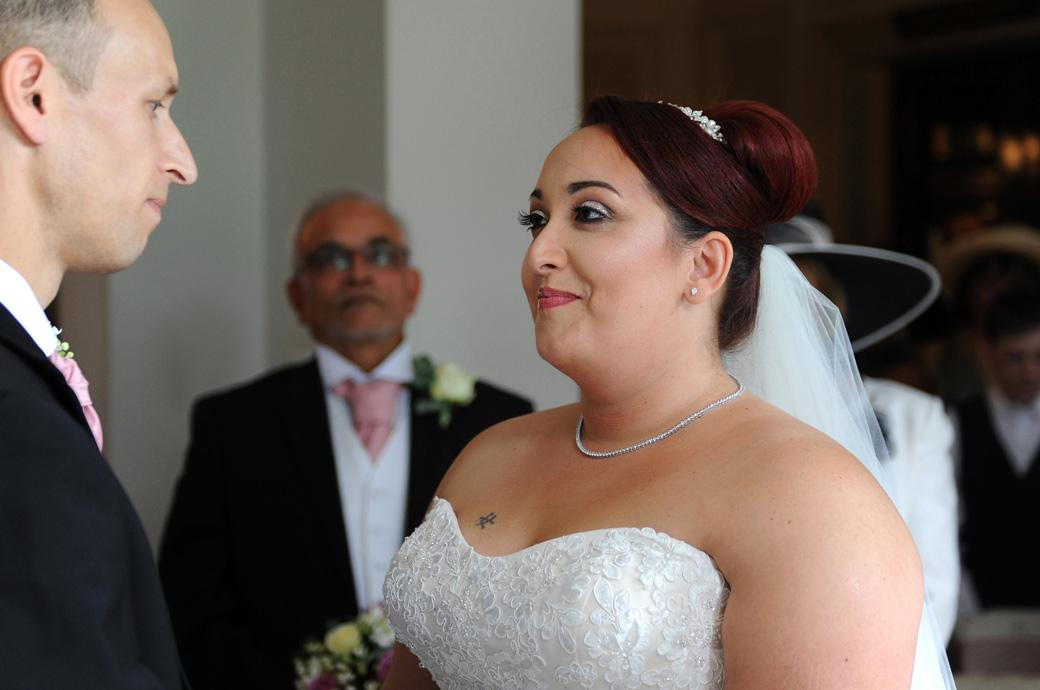 Bride smiles as she says her marriage vows to the groom during a marriage ceremony captured in The Lounge at the popular wedding venue in Surrey Gorse Hill
