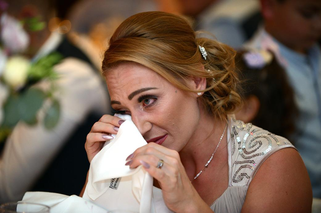 Emotional moment for a Bridesmaid captured by Surrey Lane wedding photographers as she wipes away tears at Gorse Hill during the wedding speeches